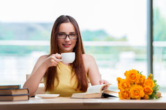 The young student drinking coffee while sudying Stock Images