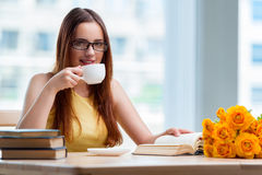 The young student drinking coffee while sudying Stock Image