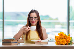 The young student drinking coffee while sudying Stock Photography