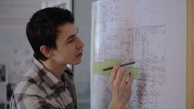 A young student engineer working on communications plan of city with pencil in hand. He's looking for flaws or errors in your plan that he will need to show stock footage