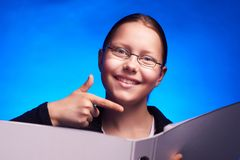 Young student in eyeglasses shows on folder with finger Stock Photography