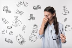 Young student feeling upset while having no money. Poor woman. Emotional sad student closing her eyes and feeling terrible while having no money for her stock photo