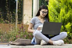 Young student female using laptop in outdoors. royalty free stock image