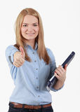 Young student girl. Portrait of an optimistic student blonde girl with her right thumb up and holding a folder in her left hand.The focus is on the eyes Stock Photo