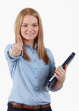 Young student girl. Portrait of an optimistic student blonde girl with her right thumb up and holding a folder in her left hand.The focus is selective on her Stock Photography