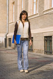 Young student girl. Beautiful young student girl walking in front of the university building Stock Photography