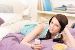 Young student girl on bed hold phone Stock Images