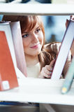 Young student girl at book shelf Stock Photos