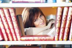 Young student girl at book shelf stock photography