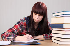 Young student girl doing homework writing in book Stock Photography