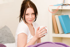 Young student girl drink coffee in bed Royalty Free Stock Image