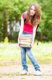Young student girl holding big pile of heavy books Stock Images