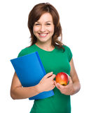 Young student girl is holding book and apple Royalty Free Stock Image