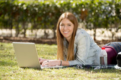 Young student girl lying on park grass with computer studying or surfing on internet Stock Photo