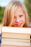 Young student girl with pile of books Royalty Free Stock Image