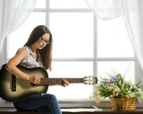 Young student girl playing music on guitar Stock Photos