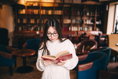 Young student girl reading book in a library. Portrait of a serious young student girl reading a book in a library alone Stock Images
