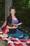 Young student girl reading a book in park. Girl with blonde hair, braided into a braid seatting on plaid Stock Image