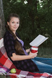 Young student girl reading a book in park. Girl with blonde hair, braided into a braid seatting on plaid Stock Photo