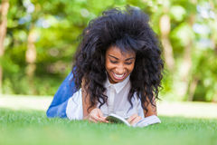 Young student girl reading a book in the school park - African p Stock Image