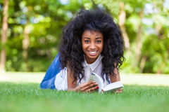 Young student girl reading a book in the school park - African p Stock Photos
