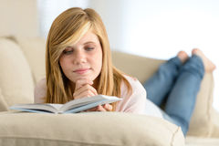 Young student girl reading book on sofa. Young student girl reading book lying on sofa Royalty Free Stock Photo