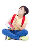 Young student girl sitting on floor with book and thinking Royalty Free Stock Photos