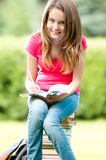 Young student girl sitting on pile of books Stock Photo