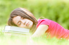 Young student girl sleeping on pile of books Royalty Free Stock Image