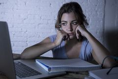 Young student girl studying tired at home laptop computer preparing exam exhausted and frustrated feeling stress Royalty Free Stock Photo