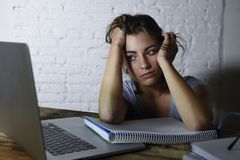 Young student girl studying tired at home laptop computer preparing exam exhausted and frustrated feeling stress. Young student girl studying late night tired at royalty free stock image
