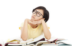 Young student girl thinking with book on the desk Stock Photos