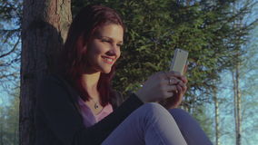 Young student girl using her smartphone in a park stock video