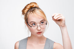 Young student girl writing on screen with pen. Young student girl in glasses writes or draws on screen with pen, face close up. High-concentrated serious and royalty free stock photo
