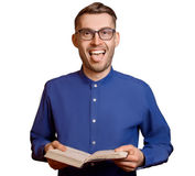 Young student in glasses and with book in hands shows tongue iso Stock Photos