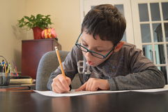 Young Student in Glasses Doing Homework Stock Photo