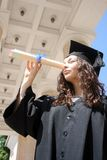 Young student in gown looking through diploma Stock Photography