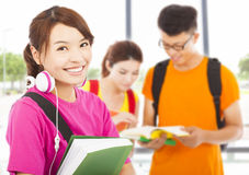 Young student holding books and earphone with classmates Stock Photos