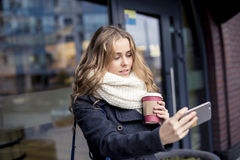 Young student holding a coffee in her hand and making Selfe on the street in winter Royalty Free Stock Images