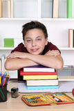 Young student holding his head on a stack of books at school Royalty Free Stock Photography