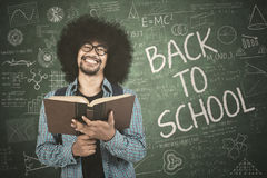 Young student holds book with doodle. Young student holding a book while standing with doodle and back to school text on chalkboard Royalty Free Stock Photography