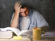 Young student at home desk reading studying at night with pile of books and coffee Stock Images