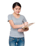 Young student jot down the information on clipboard Stock Image
