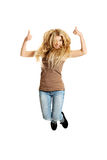 Young student jumping with thumbs up. Young casual teenager jumping with thumbs up Stock Photography