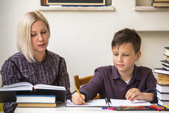 Young student learns at home with a his mom tutor. Helping. Young student learns at home with a his mom tutor royalty free stock photo
