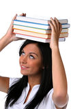 Young student learns a stack of books on the head stock photo