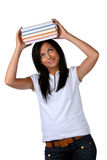 Young student learns a stack of books on the head. Young woman with a pile books on the head Stock Images