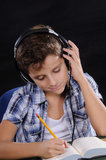 Young student listening music. Young student reading a book on a black background Stock Images