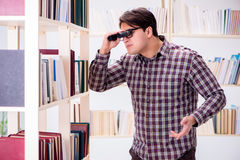 The young student looking for books in college library. Young student looking for books in college library Royalty Free Stock Photo