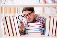 The young student looking for books in college library. Young student looking for books in college library Royalty Free Stock Images